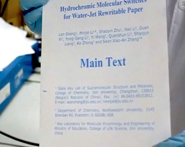 Die Forscher der Jilin Universität zeigen ein mit Wasser bedrucktes Papier. Dafür haben sie einen konventionellen Drucker umgerüstet. (Bild: Sean Zhang/Jilin Univeristät/Nature)