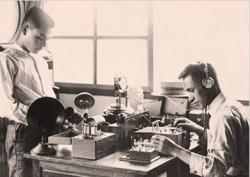 Sharp-Gründer Tokuji Hayakawa (rechts) beim Test von Radiogeräten Mitte der Zwanziger Jahre. Der Erfinder hatte zuvor einen stets scharfen mechanischen Stift (daher der Firmenname Sharp) entwickelt und auf den Markt gebracht, ehe er das Geschäft als erster Anbieter von Radios in Japan auf den Elektronikbereich ausweitete. (Bild: Sharp)