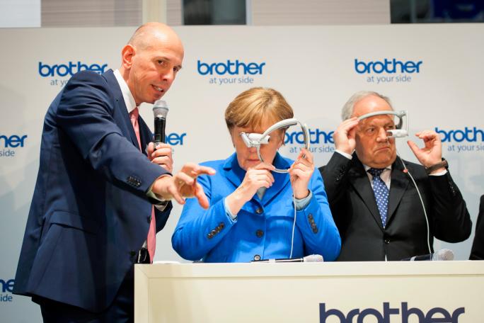 """Bild mit Symbolcharakter: Auf der diesjährigen CeBIT erklärt Matthias Kohlstrung, Geschäftsführer von Brother Deutschland, Kanzlerin Angela Merkel die Augmented-Reality-Brille """"AirScouter"""" seines Unternehmens - doch die Kanzlerin ist noch etwas ratlos, was sich mit der neuen Technologie anfangen lässt  (Bild: Bundesregierung/Güngör)."""