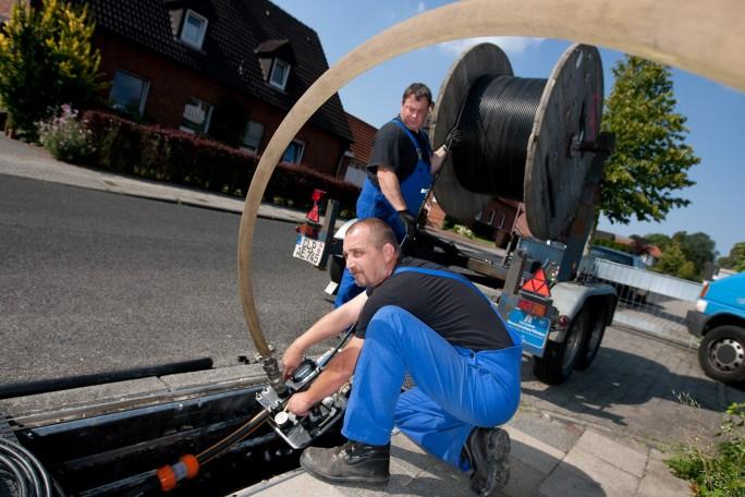EWE TEL-Mitarbeiter verlegen ein Glasfaserkabel für das lokale Telefonnetz. (Bild: friso gentsch / eye-work.com)